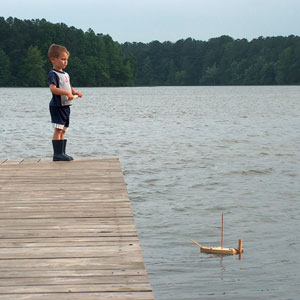a boy and his toy sailboat on a Tennessee lake