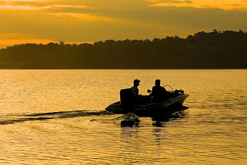 fishermen in a motorboat on a Pennsylvania lake at sunrise